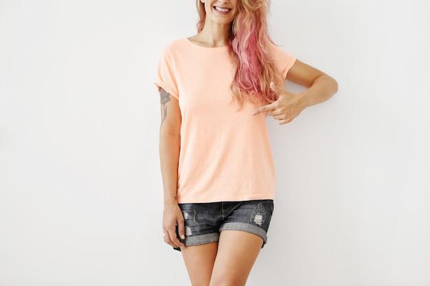 Foto recortada de elegante mulher sorridente, vestindo camiseta solta e shorts jeans, apontando para a camiseta em branco
