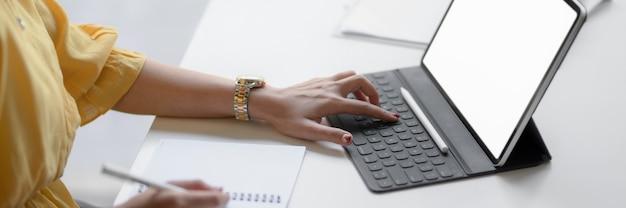 Foto recortada de empreendedor feminino, concentrando-se em seu trabalho com tablet digital