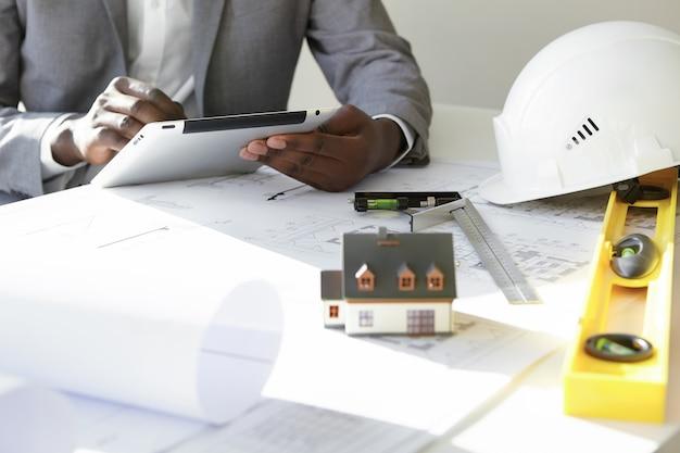 Foto recortada de empreiteiro de pele escura segurando o touchpad, inserindo dados enquanto trabalhava em um novo projeto de habitação, sentado à mesa com desenhos, casa modelo em escala, rolos de planta, régua e capacetes
