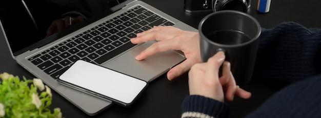 Foto recortada de empresária relaxante com café quente enquanto trabalhava com laptop e smartphone
