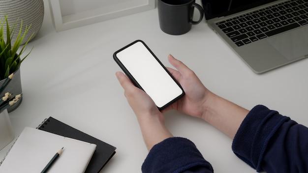 Foto recortada de empresária segurando o smartphone de tela em branco na mesa branca