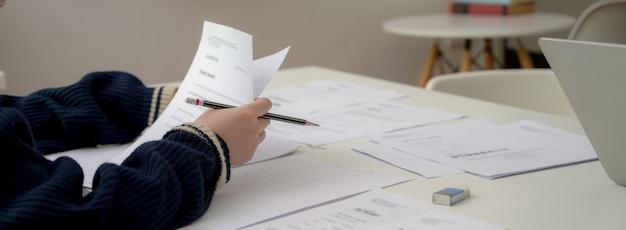 Foto recortada de empresária trabalhando com papelada financeira