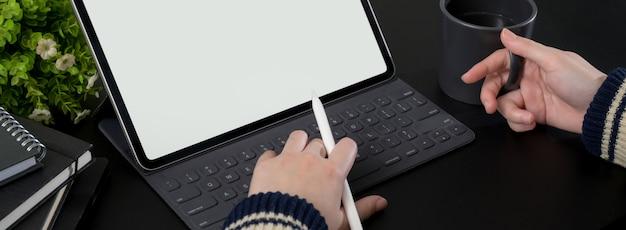 Foto recortada de empresária trabalhando no tablet de tela em branco e tomando café