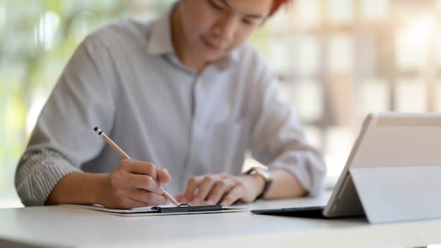 Foto recortada de empresário escrevendo uma idéia no notebook enquanto trabalhava com tablet digital