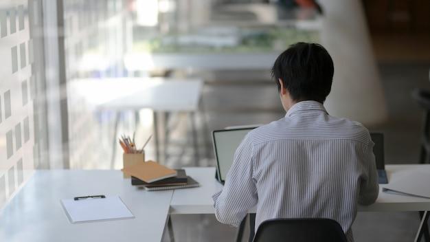 Foto recortada de empresário masculino, concentrando-se em seu trabalho com tablet digital e arquivo de documento