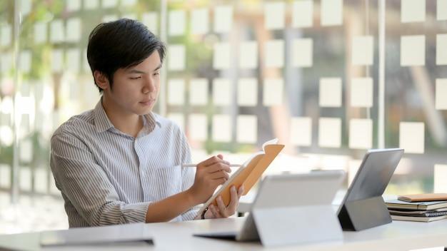 Foto recortada de empresário masculino, concentrando-se em sua tarefa na sala de escritório de parede de vidro