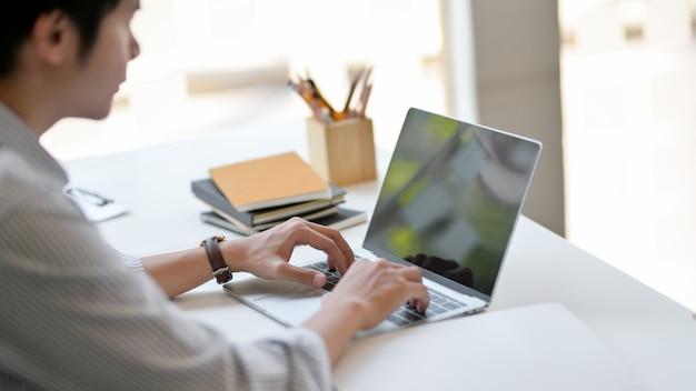 Foto recortada de empresário masculino digitando no laptop na mesa branca