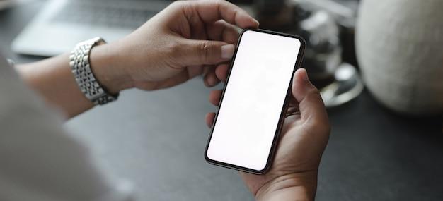 Foto recortada de empresário, olhando para o seu smartphone em branco Foto Premium