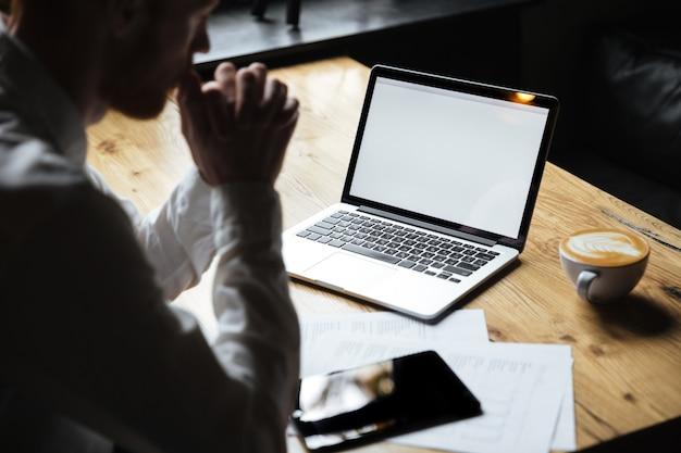 Foto recortada de empresário sentado à mesa de madeira, foco na tela do laptop