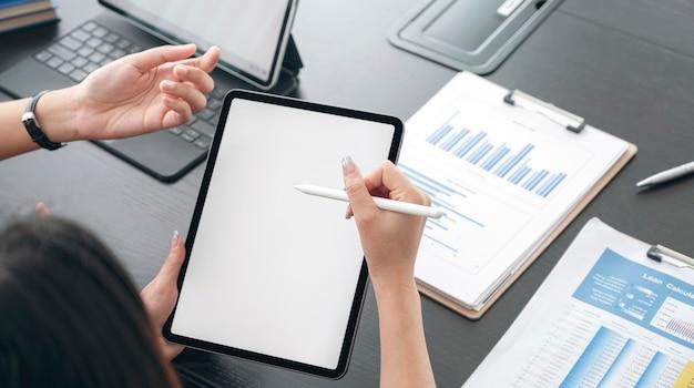 Foto recortada de empresários discutindo e trabalhando em um tablet com caneta digital, tela em branco para design gráfico.