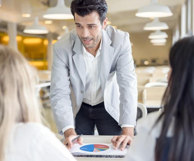 Foto recortada de empresários usando gráfico gráfico e computador portátil, tablet discutindo sobre o plano de negócios juntos no escritório moderno.