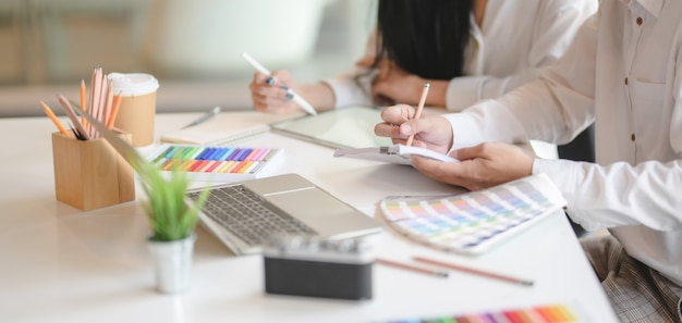 Foto recortada de equipe de intercâmbio de designers gráficos sua idéia juntos no escritório moderno