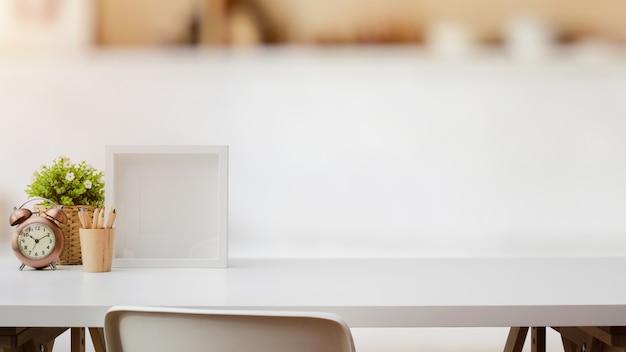 Foto recortada de espaço de trabalho com espaço de cópia, decorações, molduras e lápis de cor na mesa branca com parede branca