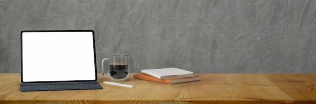 Foto recortada de espaço de trabalho confortável com tablet de tela em branco, xícara de café, livros e espaço de cópia
