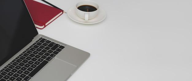 Foto recortada de espaço de trabalho mínimo com laptop, artigos de papelaria, xícara de café e cópia de espaço