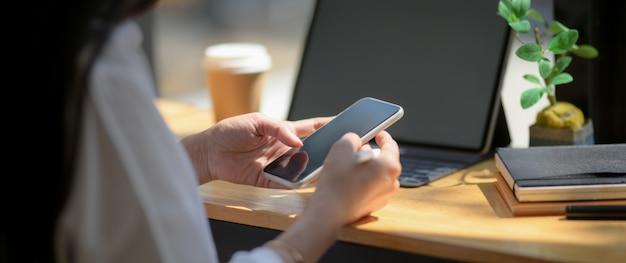 Foto recortada de estudante universitário faça uma pequena pausa com o smartphone na barra do balcão de madeira