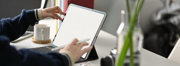 Foto recortada de estudante universitário feminino fazendo lição de casa com tablet de tela em branco