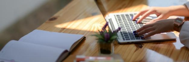 Foto recortada de estudante universitário jovem digitando no laptop com notebook e artigos de papelaria
