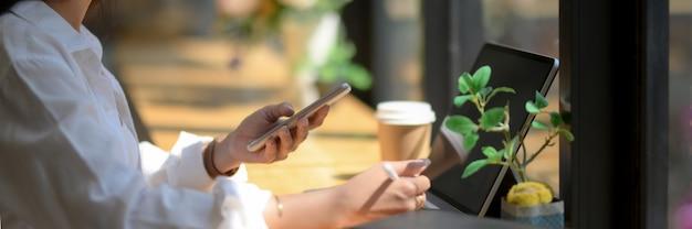 Foto recortada de estudante universitário leva pouco tempo com smartphone e tomando café