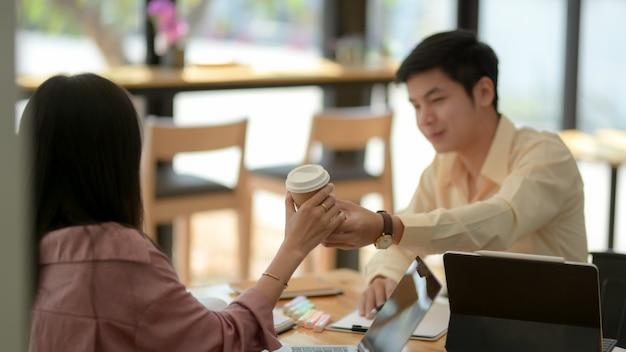 Foto recortada de estudante universitário masculino dando uma xícara de café quente para seu amigo