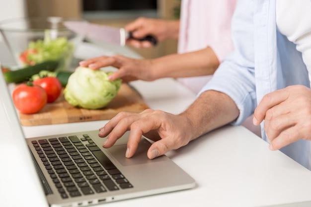 Foto recortada de família amorosa madura casal usando laptop cozinhar