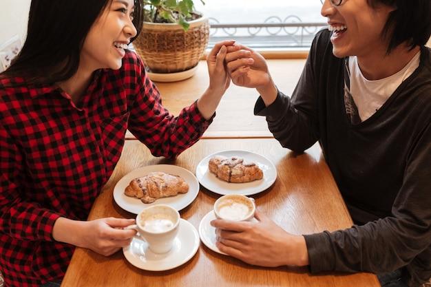 Foto recortada de feliz casal jovem sentado no café