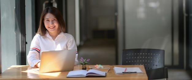 Foto recortada de feliz estudante universitário trabalhando no laptop