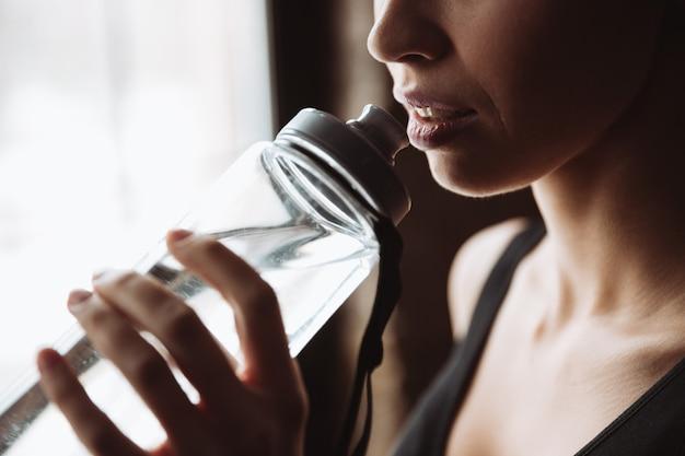 Foto recortada de fitness jovem linda mulher bebendo água.