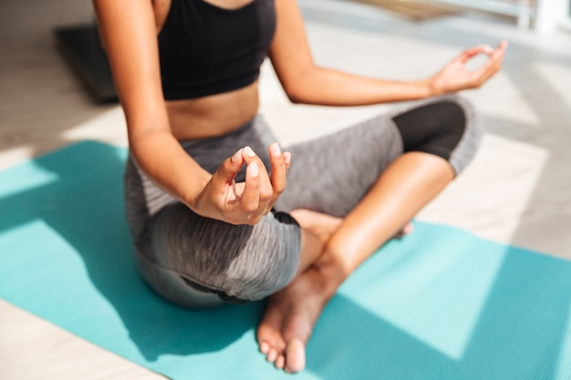 Foto recortada de fitness mulher sentada na posição de lótus