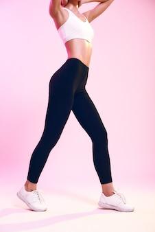 Foto recortada de forma perfeita de mulher esportiva esguia em roupas esportivas em pé contra um fundo rosa em