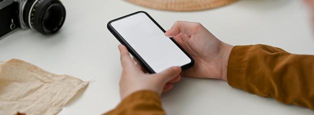 Foto recortada de fotógrafo feminino usando smartphone mock-up para entrar em contato com o cliente