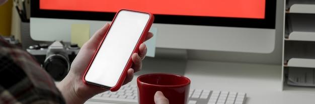 Foto recortada de freelancer feminino com o uso de smartphone de tela em branco e tomando café