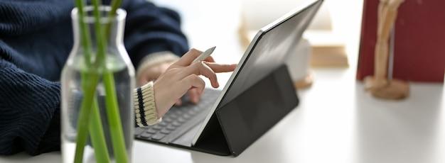 Foto recortada de freelancer feminino lendo informações sobre tablet digital