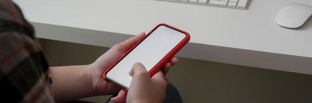 Foto recortada de freelancer feminino usando smartphone de tela em branco no espaço de trabalho