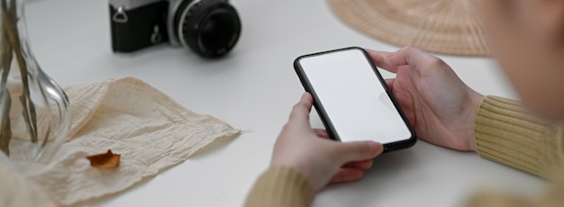 Foto recortada de freelancer feminino usando smartphone mock-up para entrar em contato com o cliente