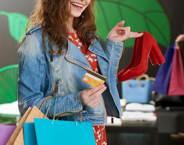 Foto recortada de garota segurando o par de sapatos vermelhos na loja