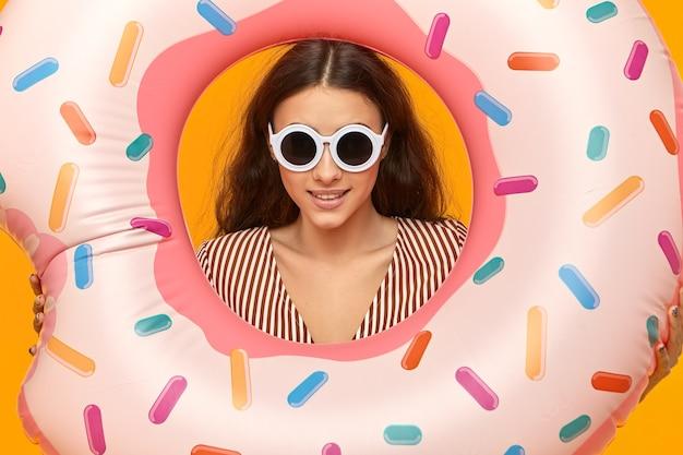 Foto recortada de glamourosa jovem atraente em tons redondos segurando um brinquedo inflável de água rosa