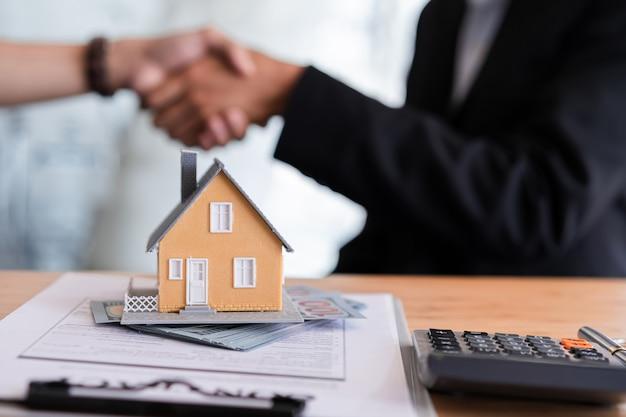 Foto recortada de handshaking de agente imobiliário com seu cliente após a assinatura do contrato e negócio bem sucedido.