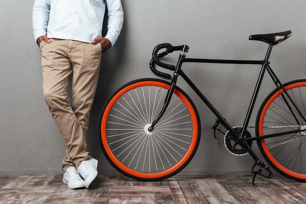 Foto recortada de homem africano em pé perto de bicicleta