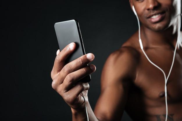 Foto recortada de homem afro-americano bonito conversando enquanto ouve música
