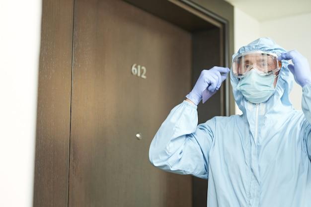Foto recortada de homem colocando óculos de segurança antes de entrar na sala. coronavírus e conceito de quarentena