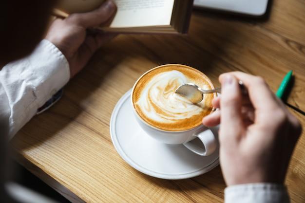 Foto recortada de homem de camisa branca, mexendo o café enquanto lê o livro