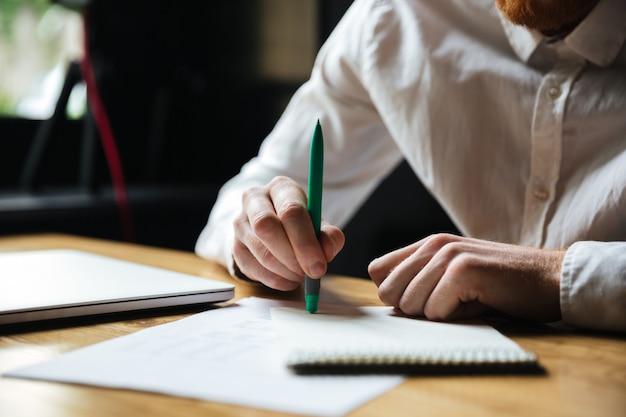 Foto recortada de homem de camisa branca, segurando a caneta verde