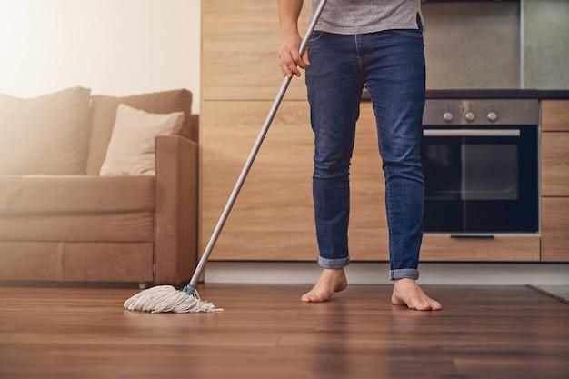 Foto recortada de homem de jeans e camiseta cinza limpando parquete com bastão especial para esfregar no apartamento