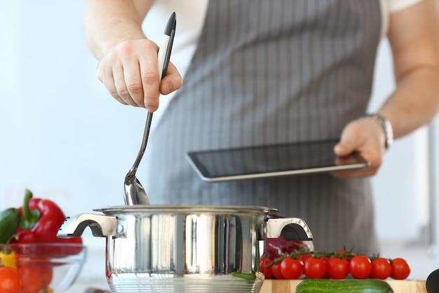 Foto recortada de homem em pé na cozinha e cozinhar