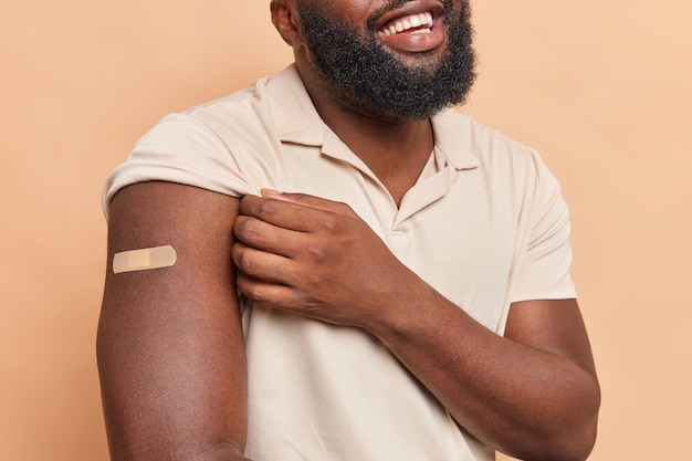 Foto recortada de homem irreconhecível com barba espessa mostra braço com gesso contente de ser vacinado cuida da saúde vestido com camiseta casual isolada sobre parede marrom