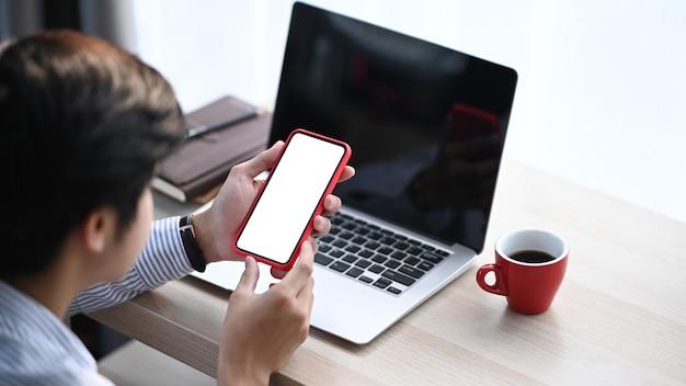 Foto recortada de homem usando telefone celular com tela em branco e sentado na frente do laptop no escritório.