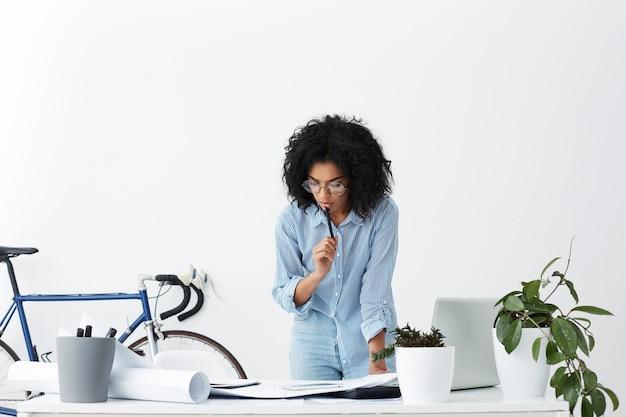 Foto recortada de interior de mulher negra em pé, encostada na mesa, tocando os lábios com uma caneta