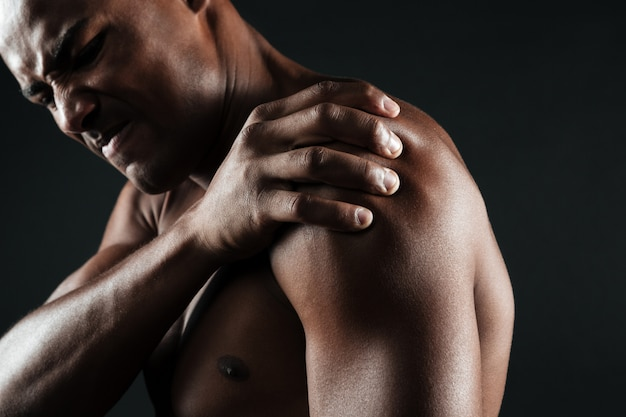 Foto recortada de jovem afro-americano sem camisa com dor no ombro