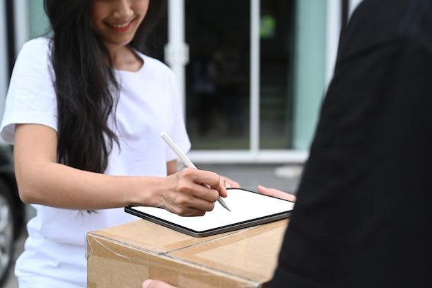 Foto recortada de jovem assinando o recibo de tablet digital da entrega do entregador.